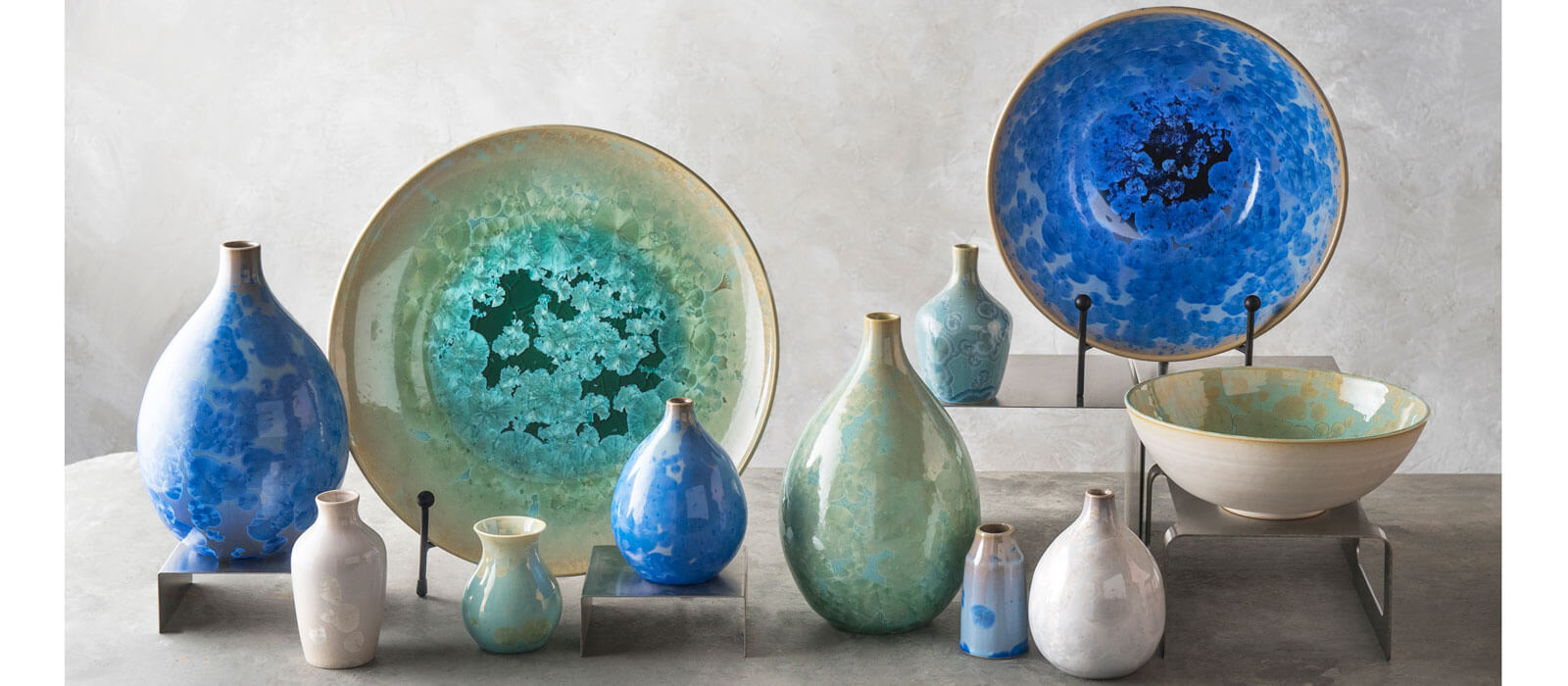 Various Crystalline products in jade and colbalt colors, including vases, bowls and platters