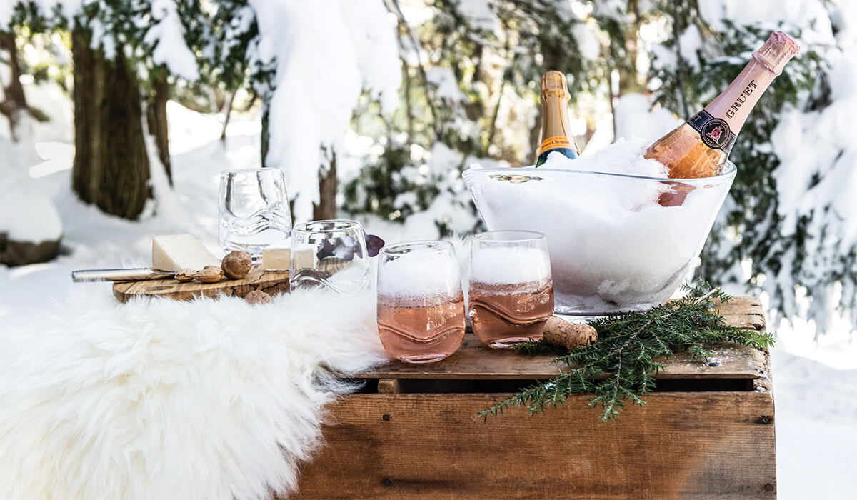 Waterbury Tumblers And Barre Bowl Filled With Champagne Against A Winter Wonderland Scene